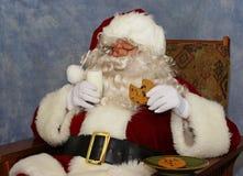 Santa tiene la leche y una galleta Fotos de archivo libres de regalías