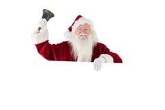 Santa tiene un segno e suona la sua campana Fotografie Stock