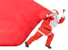 Santa tire un sac lourd Photos stock