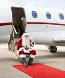 Santa Toasting Milk Glass While Sitting On Private. Full length portrait of Santa Claus toasting milk glass while sitting on private jet's ladder Royalty Free Stock Photography