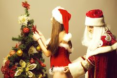 Santa touches fur on dress. Santa claus men touches fur on red dress of pretty girl decorating Christmas tree on grey wall stock images