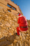 Santa trying to climb. Santa climbing a wall while a scary Halloween monster is waiting for him Stock Photos