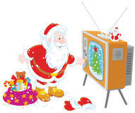 Santa turning on his TV Royalty Free Stock Images