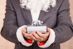 Santa In Txedo Hold A Gift Box. Business Santa Hold A Red Gift Box Royalty Free Stock Images