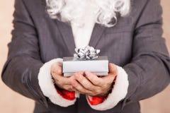 Santa In Txedo Hold una caja de regalo Imágenes de archivo libres de regalías