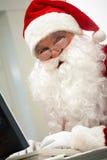 Santa typing. Portrait of Santa Claus typing and looking at camera stock image