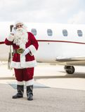 Santa Using Cell Phone Against Private Jet. Full length of Santa Claus using cell phone against private jet at airport terminal Royalty Free Stock Image