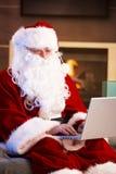 Santa using computer Royalty Free Stock Image
