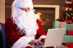 Santa using computer. Modern Santa Claus sitting by fireplace using computer computer Stock Photos