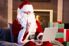 Santa using computer. Modern Santa Claus sitting by fireplace using computer computer Royalty Free Stock Photo