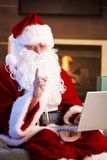 Santa using computer Stock Photography