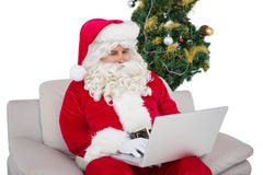 Santa using his laptop on the couch Stock Photos