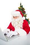 Santa using his laptop near christmas tree Royalty Free Stock Photo