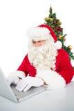 Santa using his laptop near christmas tree Royalty Free Stock Photo