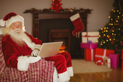 Santa using laptop on the couch at christmas Royalty Free Stock Photos