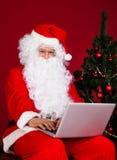 Santa using laptop Stock Photo