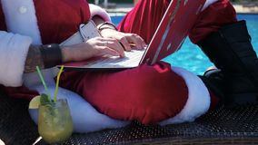 Santa using laptop and typing near swimming pool. Person in christmas wear imitation the Santa costume using laptop sitting on the chaise at swimming pool and stock video