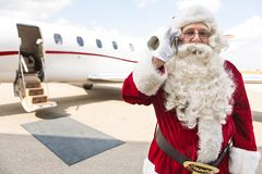 Santa Using Mobile Phone Against Private Jet. Portrait of Santa Claus using mobile phone against private jet at airport terminal Stock Photography