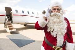 Santa Using Mobile Phone Against-Privatjet Stockfotografie