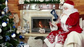 Santa using tablet, papa noel sitting in chair with electronic device, room with fireplace stock video footage