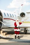 Santa Using Waving Against Private Jet. Full length of Santa Claus waving against private jet at airport terminal Royalty Free Stock Photos