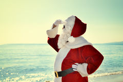 Santa Vacation - Happy Santa on the Beach Looking Around Royalty Free Stock Images