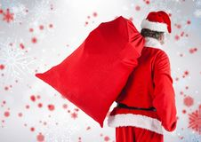 Santa walking with gift sack. Against digitally generated background Stock Photos