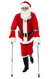 Santa walking with the help of crutches. Male santa claus walking with help of crutches Royalty Free Stock Image