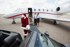 Santa walking up to private jet. Santa leaving convertible car and walking up to jet Stock Image