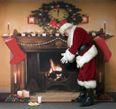 Santa Warming By The Fireplace Royalty Free Stock Photos