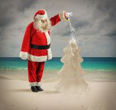 Santa watering a Christmas tree Royalty Free Stock Photography