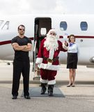 Santa Waving Hand Against Private Jet Stock Photo