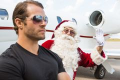 Santa Waving Hand With Bodyguard In Foreground. Portrait of Santa waving hand with bodyguard in foreground against private jet at airport terminal royalty free stock photo