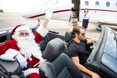 Santa Waving Hand While Chauffeur Driving Royalty Free Stock Photos