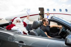 Santa Waving Hand While Driver Driving Convertible Royalty Free Stock Image
