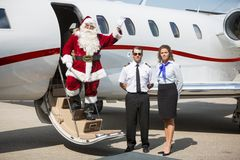 Santa Waving Hand On Private Jet. Portrait of Santa waving hand on private jet's ladder while pilot and airhostess standing by Royalty Free Stock Image
