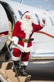 Santa Waving Hand While Standing On Private Jet's. Full length portrait of Santa waving hand while standing on private jet's ladder at airport terminal Stock Image