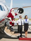 Santa Waving On Private Jet. Full length of Santa waving hand on ladder of private jet Royalty Free Stock Images