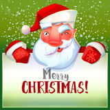 Santa winks and holding typography card Stock Photo