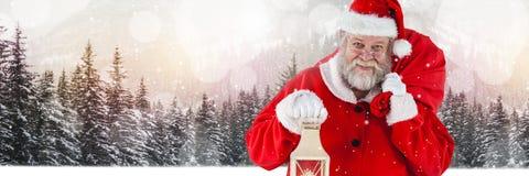 Santa with Winter landscape holding lantern and sack Stock Image