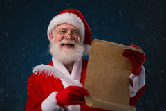 Santa with wish list. Happy Santa Claus reading a letter or a wish list Royalty Free Stock Image
