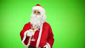 Santa wishes a merry Christmas and drinks a glass of champagne. chroma key