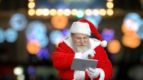 Santa is wishing well by using the tablet. stock footage