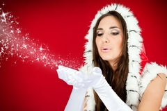 Santa woman blowing snow from her hands. Attractive woman blowing snow from her hands Royalty Free Stock Photo