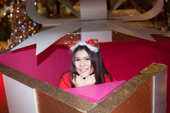Santa woman dressing in a large gift box. Stock Image