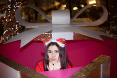 Santa woman dressing in a large gift box. Royalty Free Stock Photos