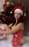 Santa woman helper sitting next to Christmas tree Stock Photo