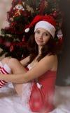 Santa woman helper sitting next to Christmas tree stock photo