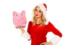 Santa woman holding a piggy bank Stock Images
