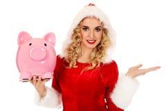 Santa woman holding a piggy bank Stock Photography